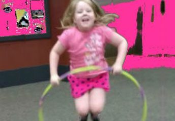 Girl jumping through a hoop